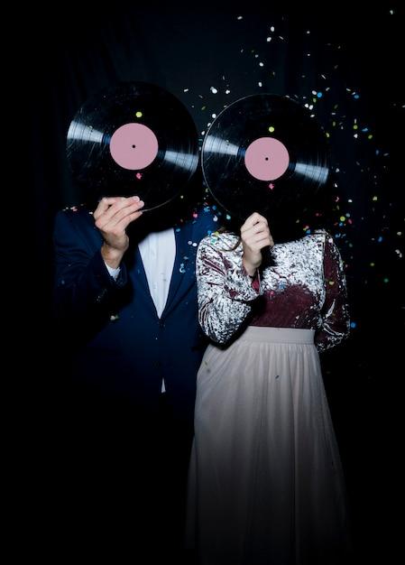 Casal cobrindo rostos com discos de vinil na festa Foto gratuita