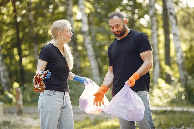 Casal coleta lixo em sacos de lixo no parque Foto gratuita