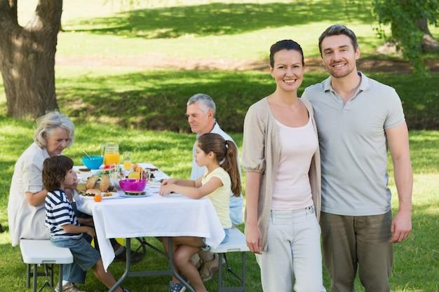 Casal com a família almoçando no gramado Foto Premium