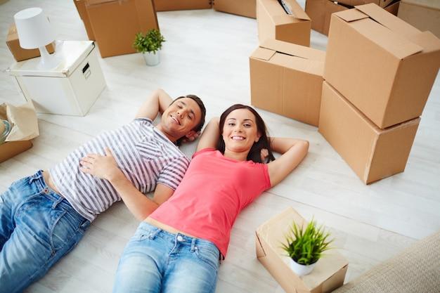 Casal com a sala cheia de caixas Foto gratuita