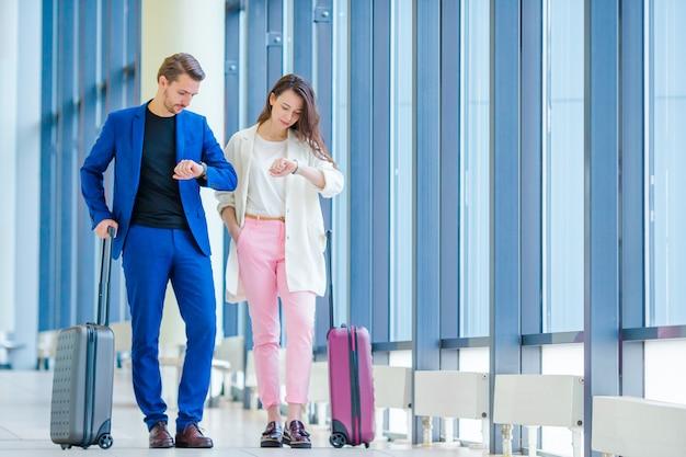 Casal com bagagem no aeroporto internacional, correndo para um voo para aterrar. homem e mulher olhando no relógio interior perto de grande janela Foto Premium