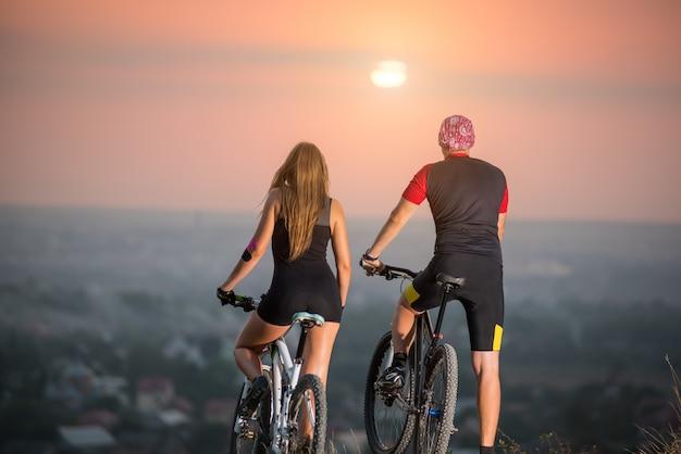 Casal com bicicletas esportivas ao pôr do sol Foto Premium