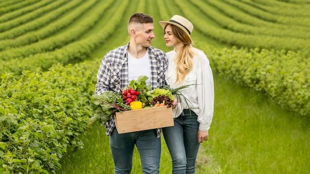 Casal com cesta de legumes em terras agrícolas Foto gratuita