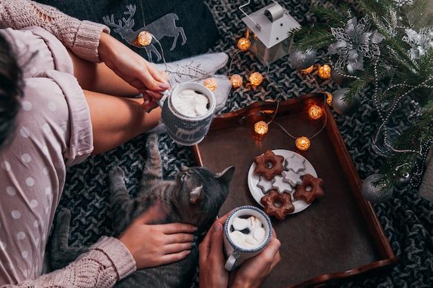 Casal com chocolate quente debaixo da árvore de natal Foto Premium