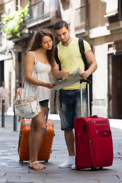 Casal com mapa de leitura de bagagem Foto gratuita