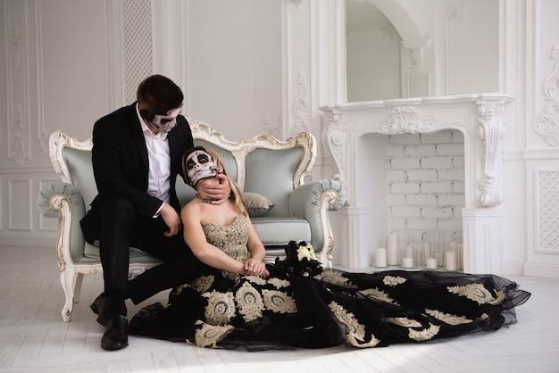 Casal com maquiagem de caveira escura sobre fundo branco. dia das bruxas Foto Premium
