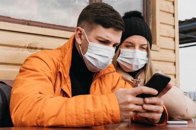 Casal com máscaras e smartphone Foto gratuita