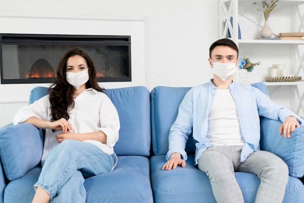 Casal com máscaras em casa no sofá Foto gratuita