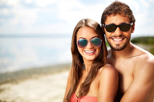 a55a8448c7507 Casal com óculos de sol na praia