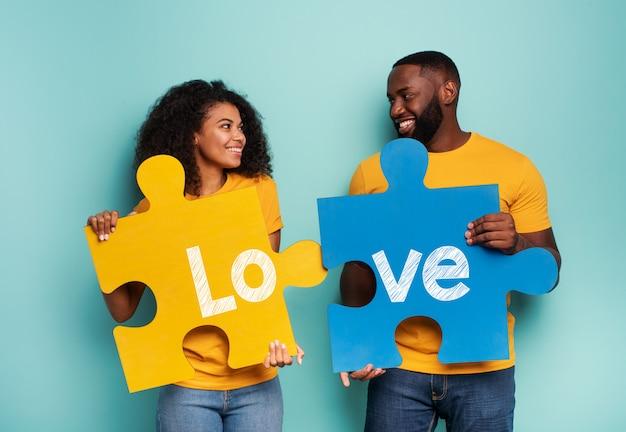 Casal com quebra-cabeças na mão sobre fundo azul claro. conceito de integração, união, relacionamento e parceria Foto Premium