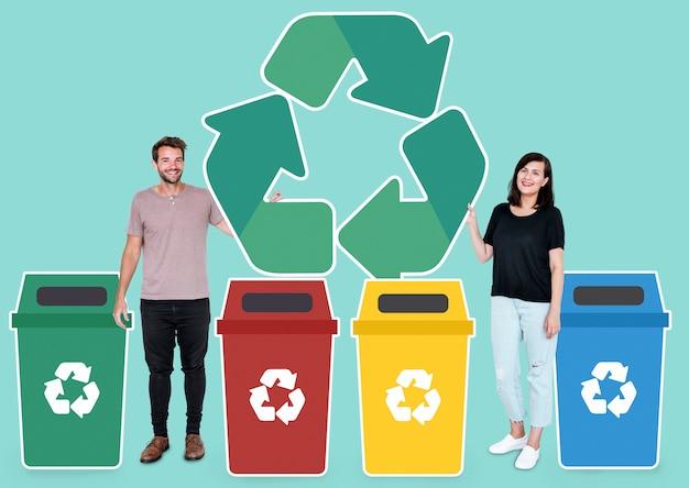 Casal com um símbolo de reciclagem e lixeiras Foto Premium