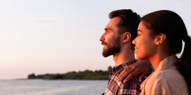 Casal com vista lateral apreciando o pôr do sol com espaço de cópia Foto gratuita