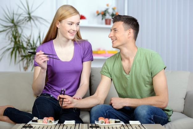 Casal comendo sushi enquanto está sentado perto do outro. Foto Premium