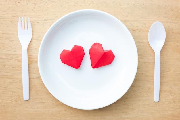 Casal coração de origami vermelho no prato branco, amor e conceito de dia dos namorados Foto Premium