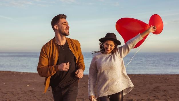 Casal correndo na beira-mar com balões de coração vermelho Foto gratuita