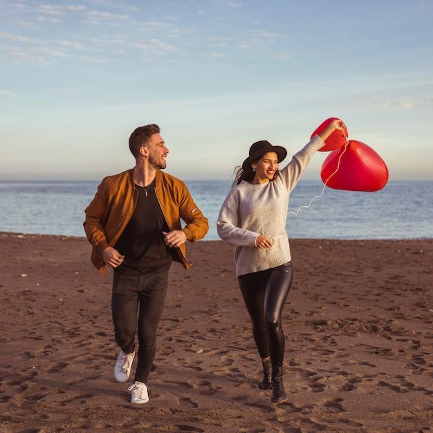 Casal correndo na beira-mar com balões de coração Foto gratuita