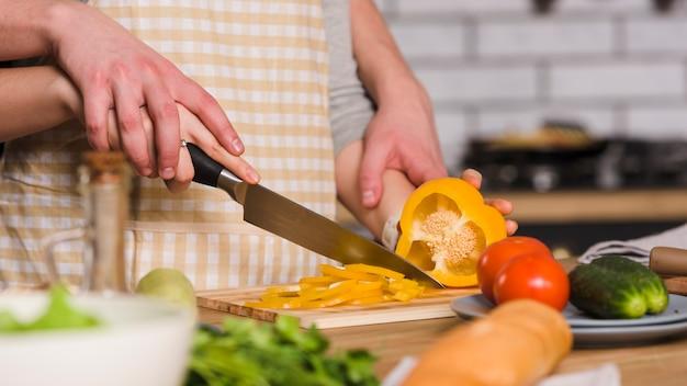 Casal cortando pimenta na cozinha juntos Foto gratuita