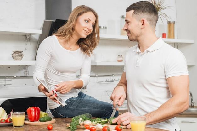 Casal cozinhando com tablet em casa Foto gratuita