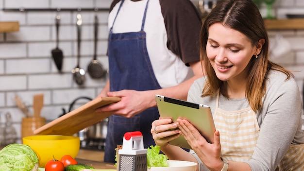Casal cozinhar alimentos usando tablet Foto gratuita