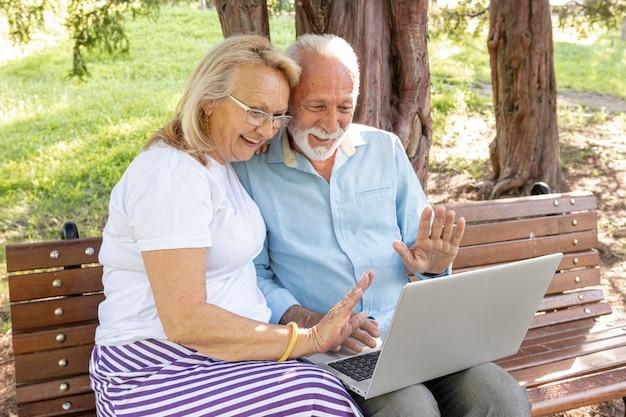 Casal cumprimentando alguém no laptop Foto gratuita