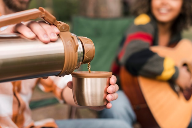 Casal curtindo acampar ao ar livre com violão e bebida quente Foto gratuita