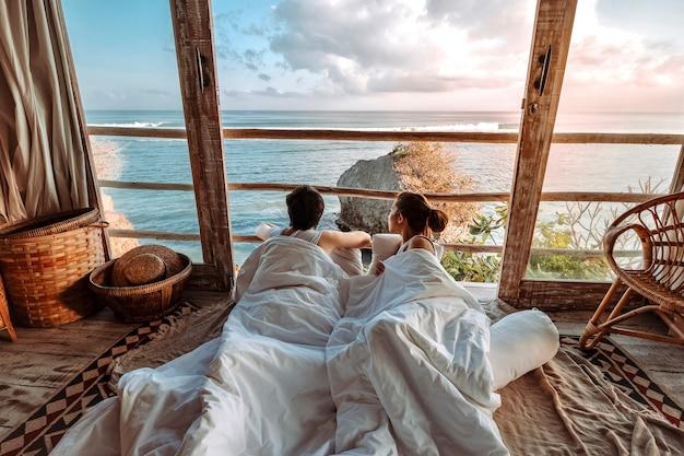 Casal curtindo férias de manhã no bangalô de praia tropical, olhando para o oceano vista férias relaxantes em uluwatu bali, indonésia Foto Premium