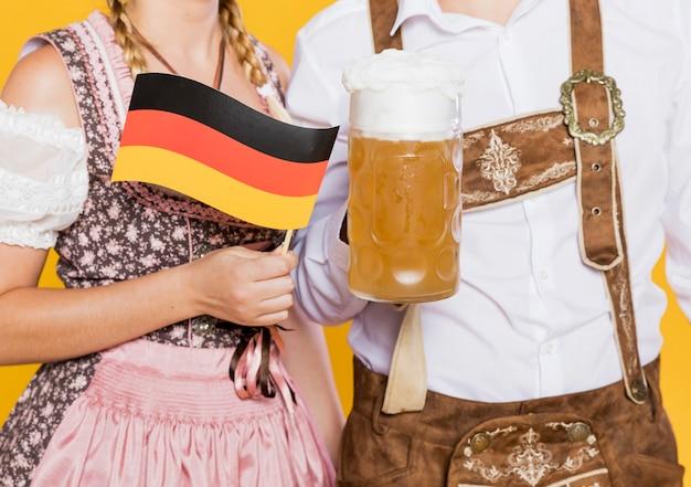 Casal da baviera com cerveja e bandeira Foto gratuita