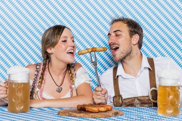 Casal da baviera degustação bratwurst deliciosa Foto gratuita