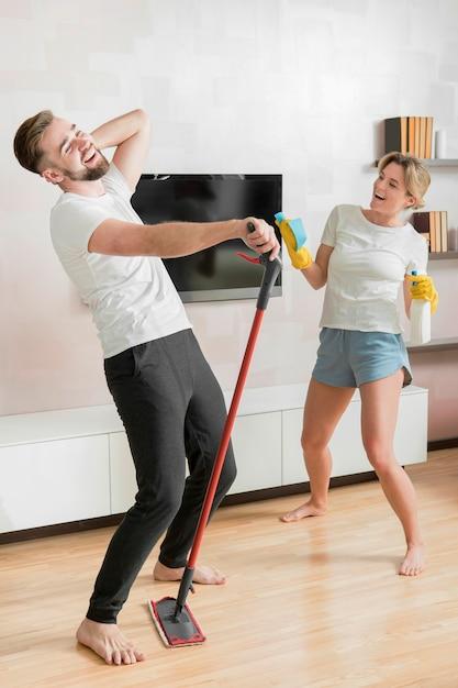 Casal dançando dentro de casa com produtos de limpeza Foto gratuita