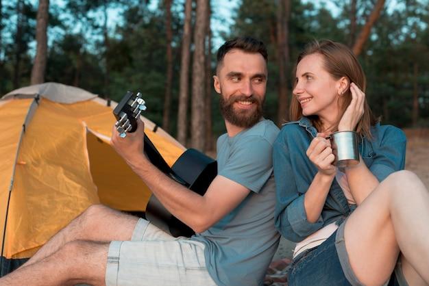 Casal de acampamento de costas olhando para o outro Foto gratuita