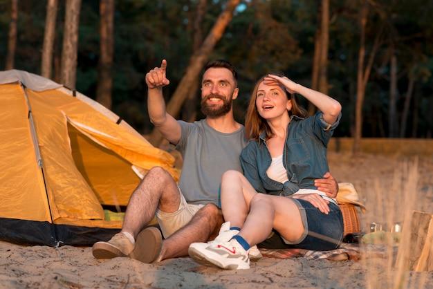 Casal de acampamento olhando para o céu Foto gratuita