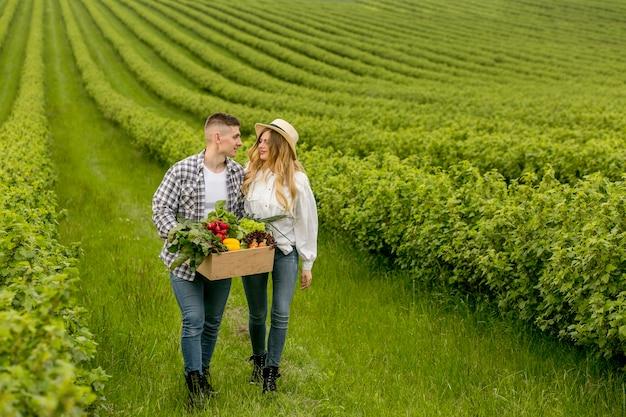 Casal de alto ângulo com cesta de legumes Foto gratuita