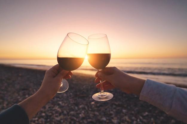 Casal de amantes, bebendo vinho tinto durante assistir o pôr do sol e curtir férias no mar em lua de mel Foto Premium