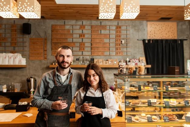 Casal de aventais posando com xícaras de café Foto gratuita