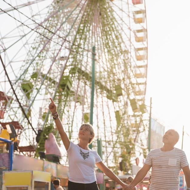 Casal de baixo ângulo com roda gigante Foto gratuita