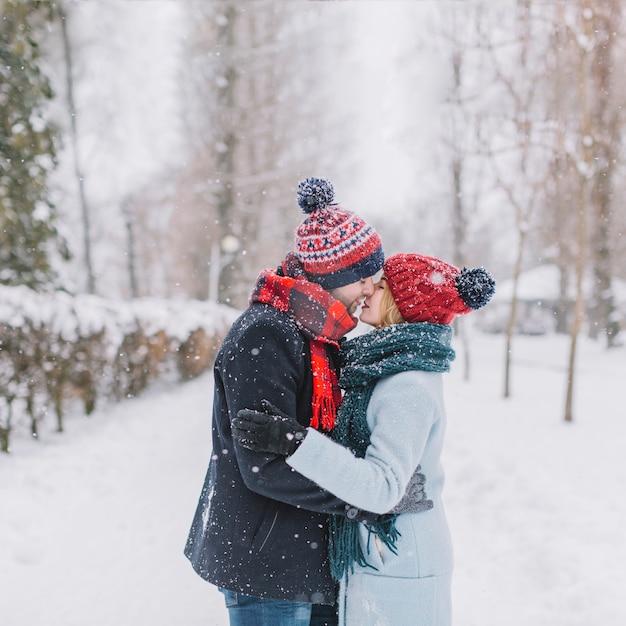 Casal de beijo surpreendente na neve caindo Foto gratuita