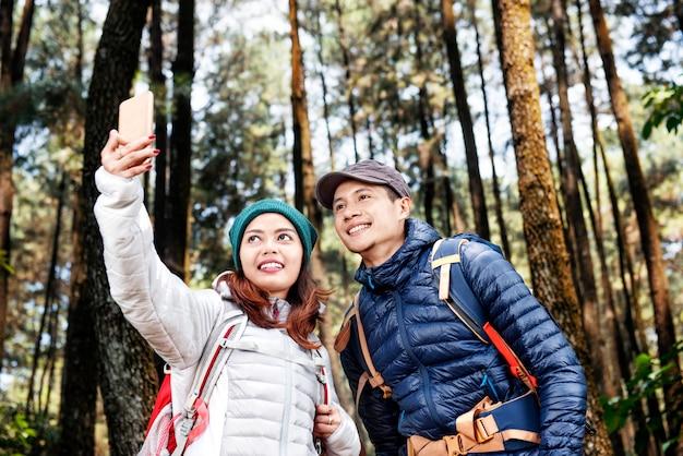 Casal de caminhantes asiáticos atraentes tirando foto de selfie com telefone móvel Foto Premium
