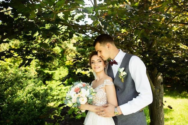 Casal de casamento incrível posando em um fundo verde natural Foto Premium