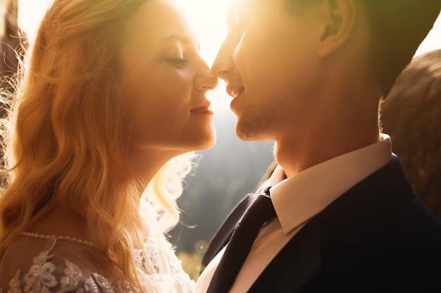 Casal de casamento romântico conto de fadas beijando ao pôr do sol Foto Premium