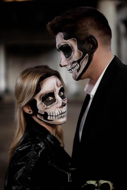 Casal de dia das bruxas, vestido com roupas de casamento zumbi romântico Foto Premium