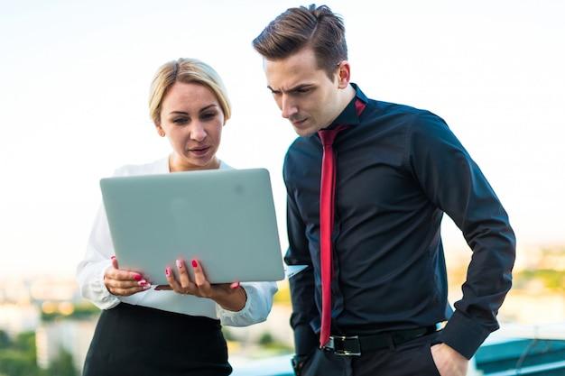 Casal de empresários, homem morena séria e atraente mulher loira ficar no telhado e olhar no laptop Foto Premium