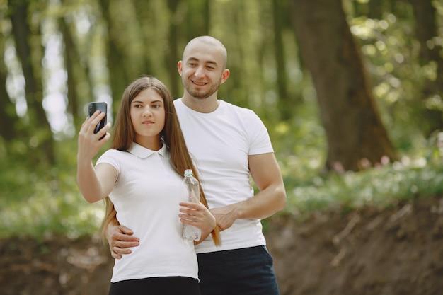 Casal de esporte passa o tempo em uma floresta de verão Foto gratuita