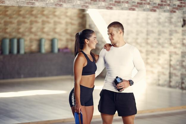 Casal de esportes em um treinamento de sportswear em uma academia Foto gratuita