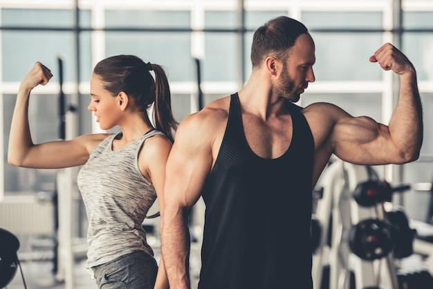 Casal de esportes lindo está mostrando seus músculos. Foto Premium