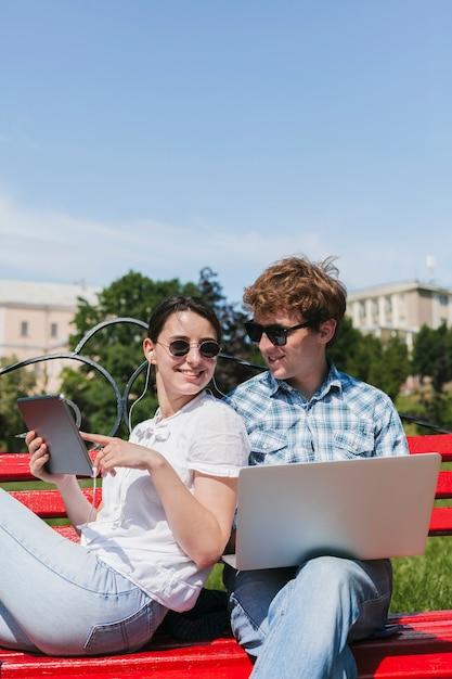 Casal de freelancers feliz no parque Foto gratuita