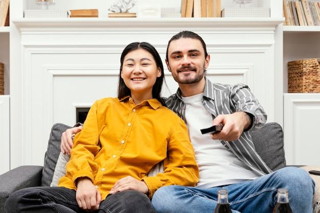 Casal de frente para o sofá sentado no sofá assistindo tv Foto gratuita