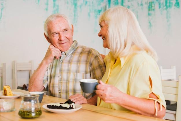 Casal de idosos alegres bebendo chá e conversando Foto gratuita