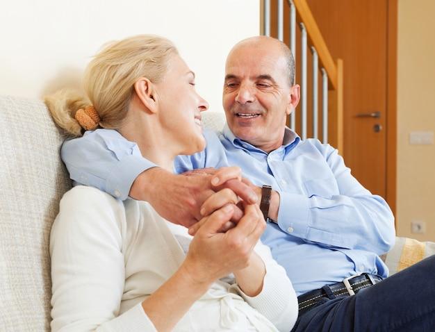 Casal de idosos alegres juntos no sofá no interior da casa Foto gratuita