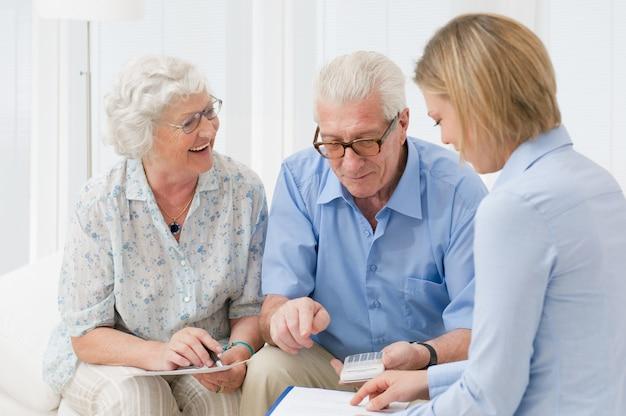 Casal de idosos aposentados planejando seus investimentos com um consultor financeiro Foto Premium
