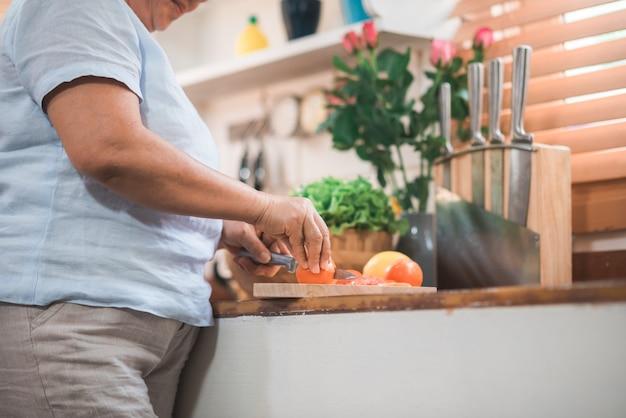 Casal de idosos asiáticos cortar tomates preparar ingrediente para fazer comida na cozinha Foto gratuita